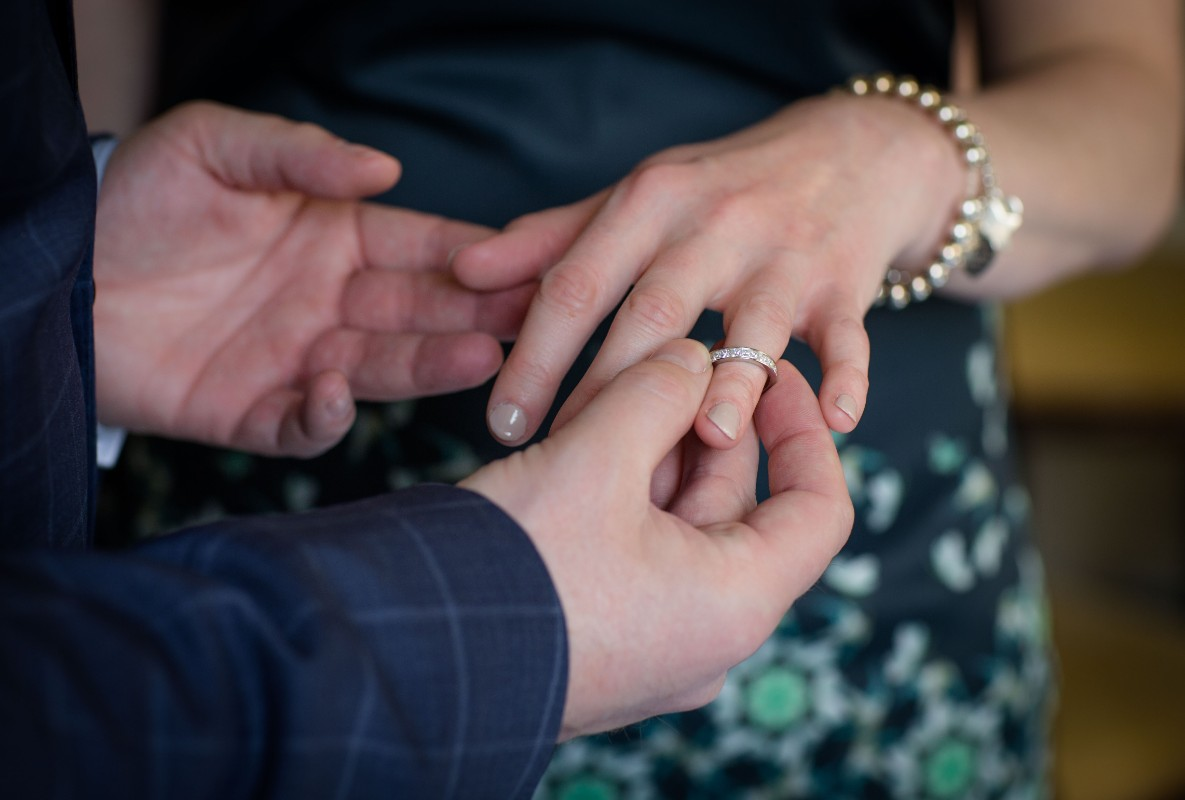 groom putting wedding ring on his bride's ring finger during the ceremony
