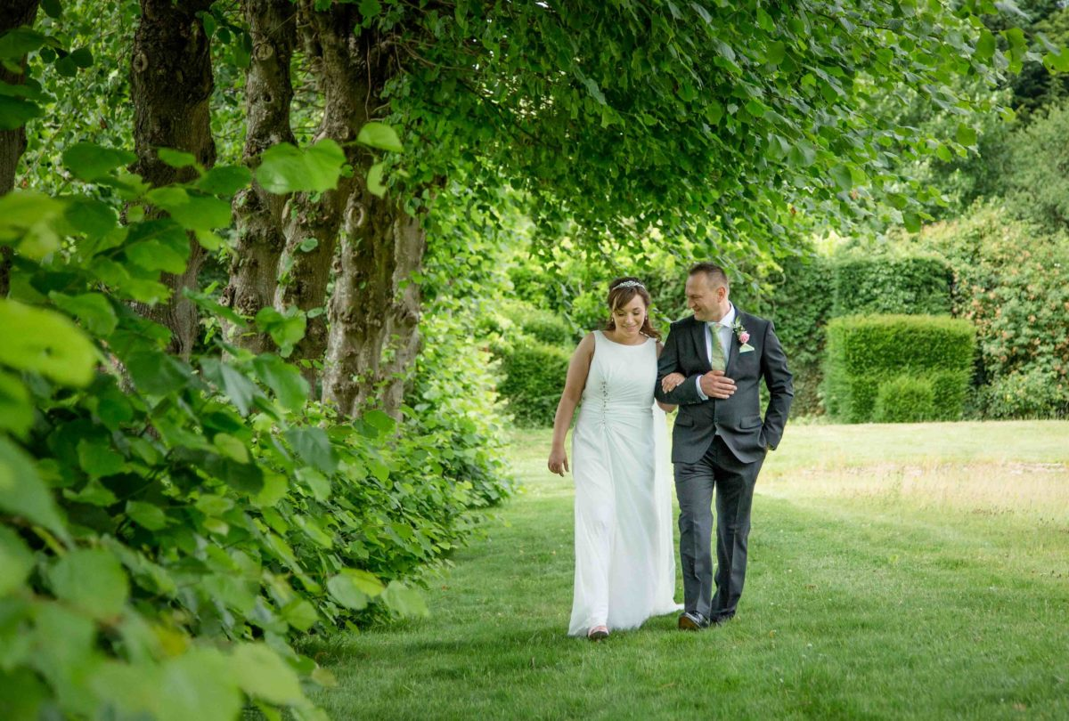 bride and groom walking beside the lime tree avenue at Stanton House Hotel, Swindon, Wiltshire