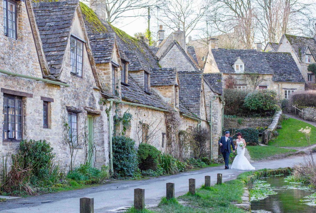 bride and groom walking beside Arlington Row in Bibury, Gloucestershire