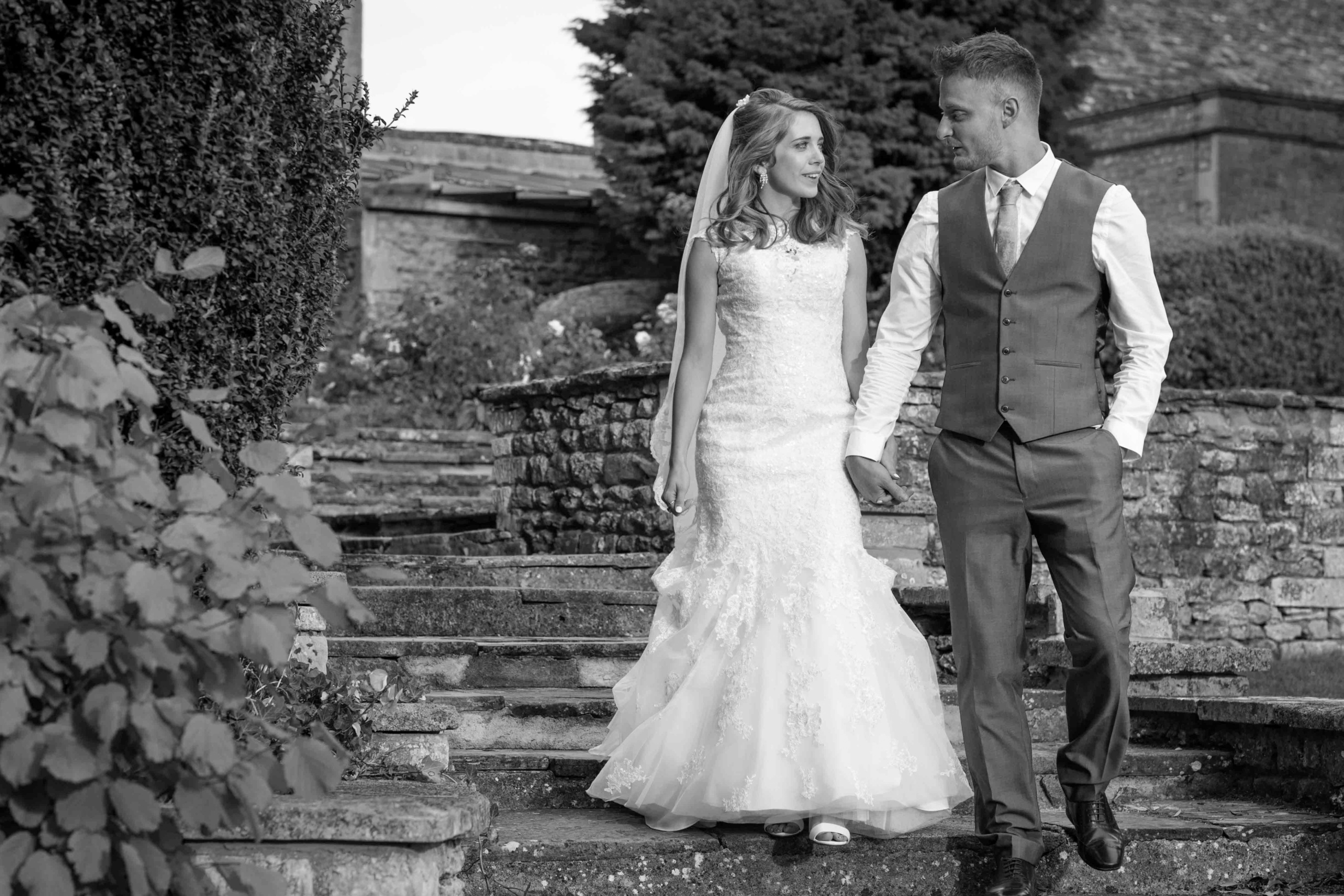 Stanton House Hotel, Wiltshire, Wedding Photography, Black and White, in grounds, Bride and Groom walking down stone steps holding hands and looking into each others eyes