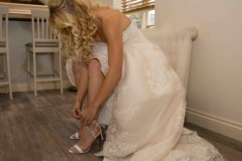 Caswell House, Oxfordshire, Bride Sat Adjusting Shoe