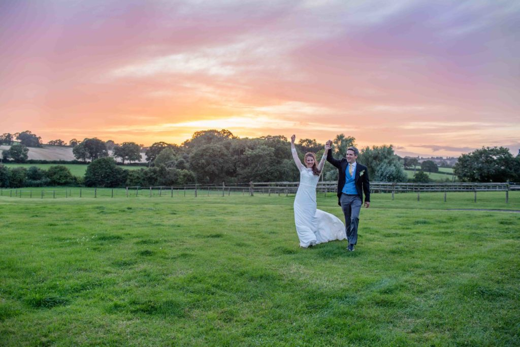 Cotswolds Wedding Photography, Bride and Groom holding hands arms raised walking across grass field with sunset in the background, Mintridge, Herefordshire