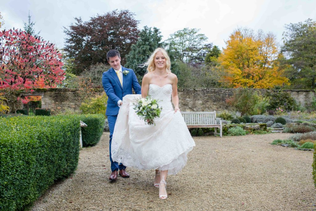 Caswell House, Oxfordshire, Groom Holding Bride Dress Walking