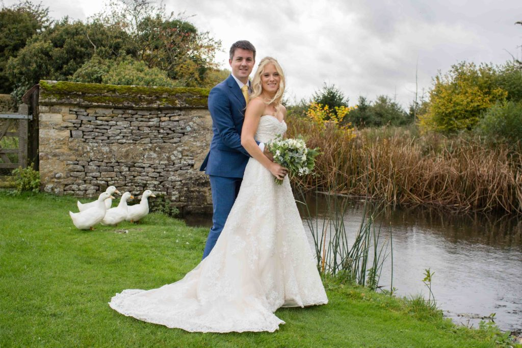 Wedding Photography Cotswolds, Caswell House, Oxfordshire, Groom hugging Bride from behind stood next to lake with ducks and stone bridge in background