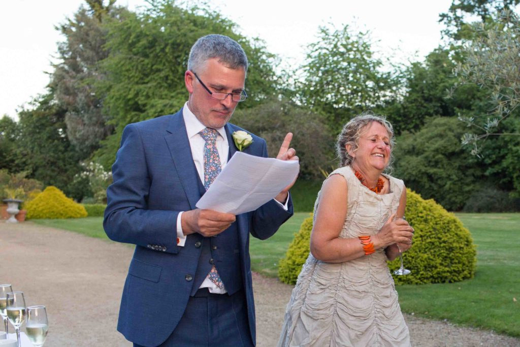 Manor by the Lake, Cheltenham, Wedding, Bride Laughing Groom Reading Speech Grounds