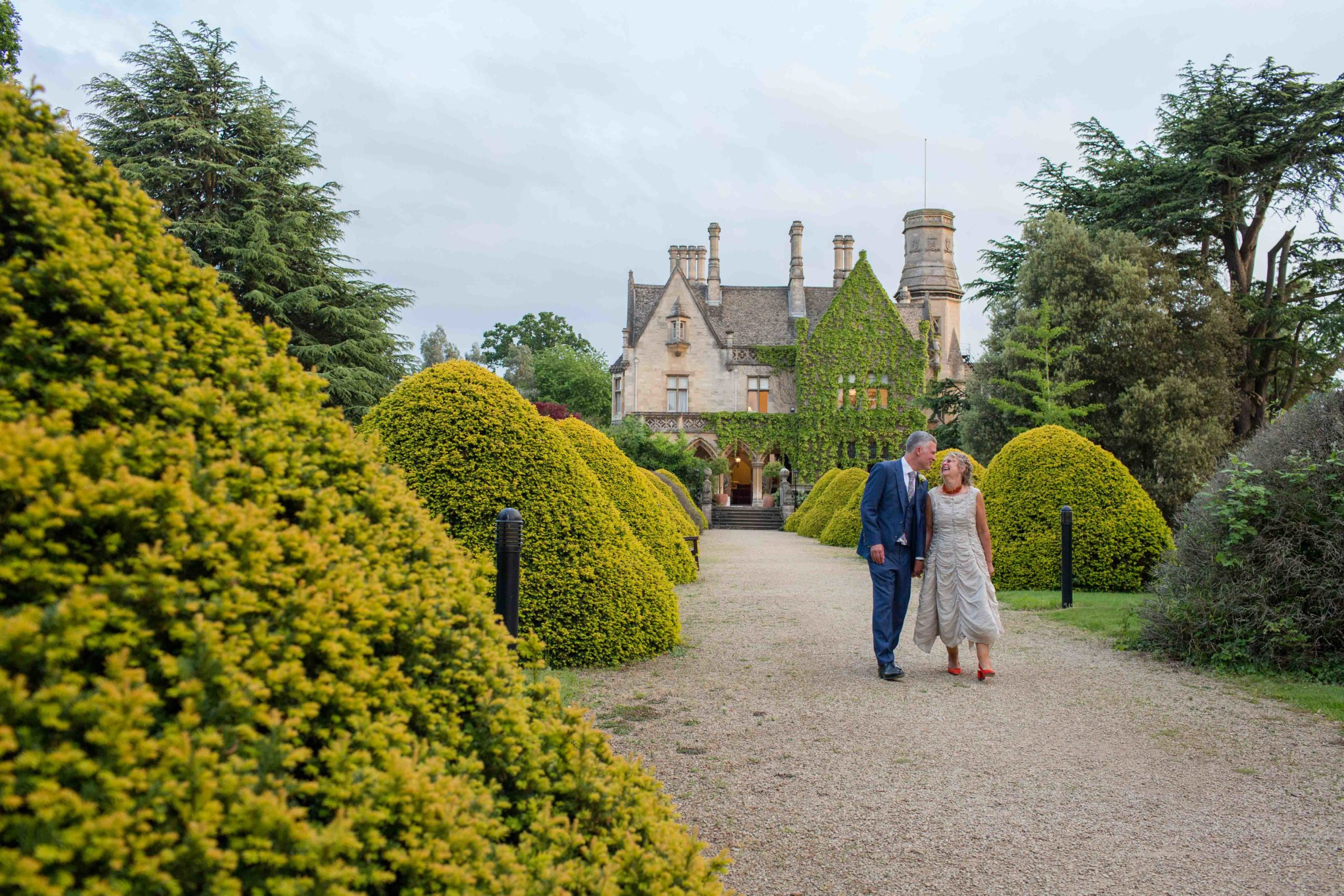 Cotswolds Wedding Photographer, Manor by the lake, Gloucestershire, Bride and Groom walking down wide stone chip path lined with green ornamental bushes and Manor in the background.