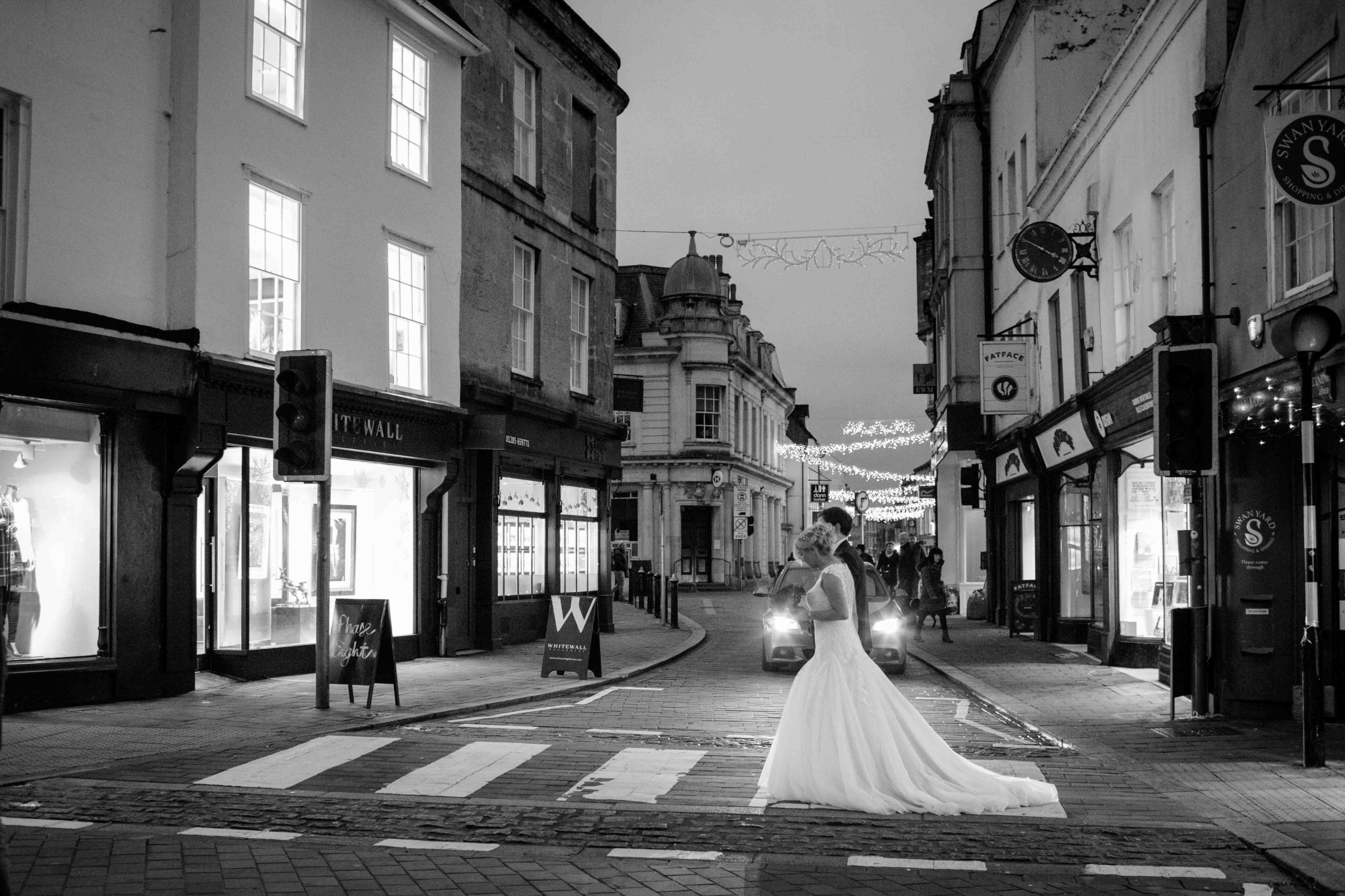 Cotswolds Wedding Photography, Bride and Groom holding hands walking across zebra crossing, Cirencester market square.