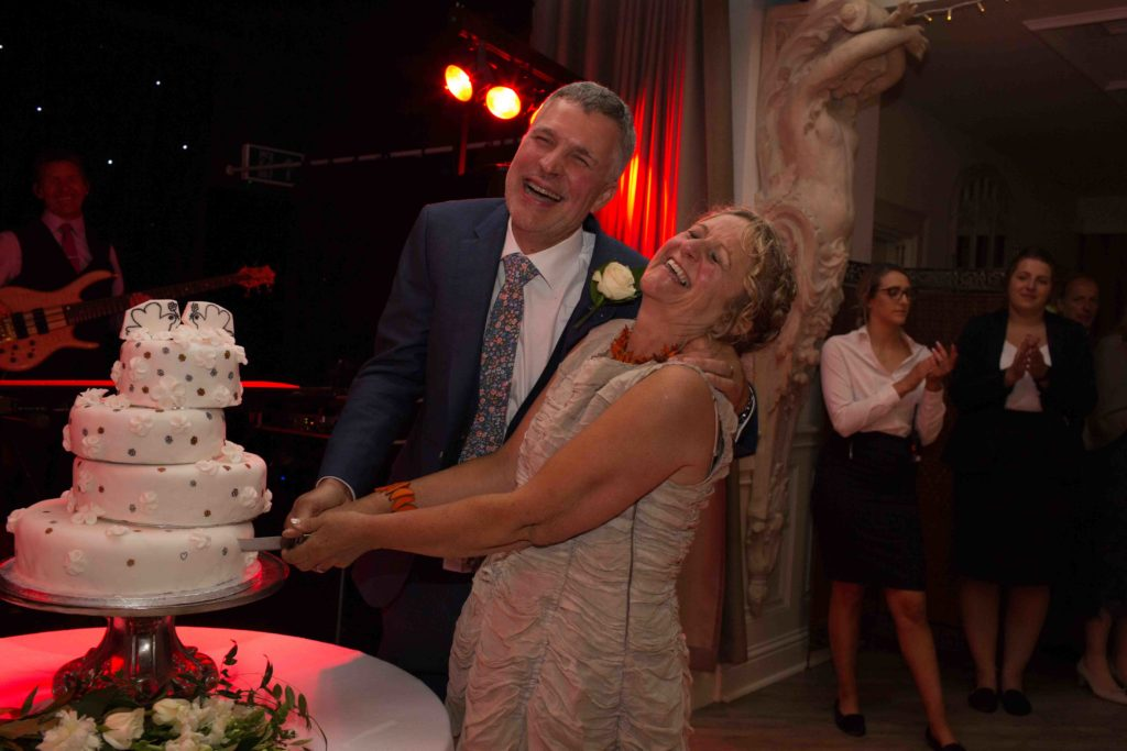 Manor by the Lake, Cheltenham, Wedding, Bride Groom Cutting Cake Laughing