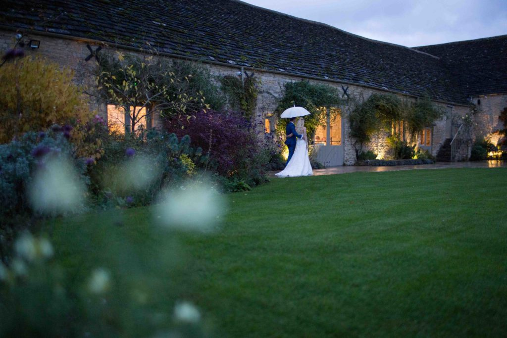 Caswell House, Oxfordshire, Bride Groom Umbrella Outside Long