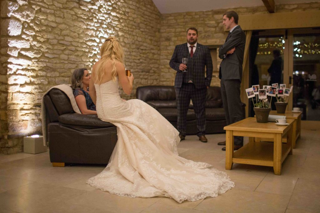 Caswell House, Oxfordshire, Bride Sat Arm Chair Chatting with Guests