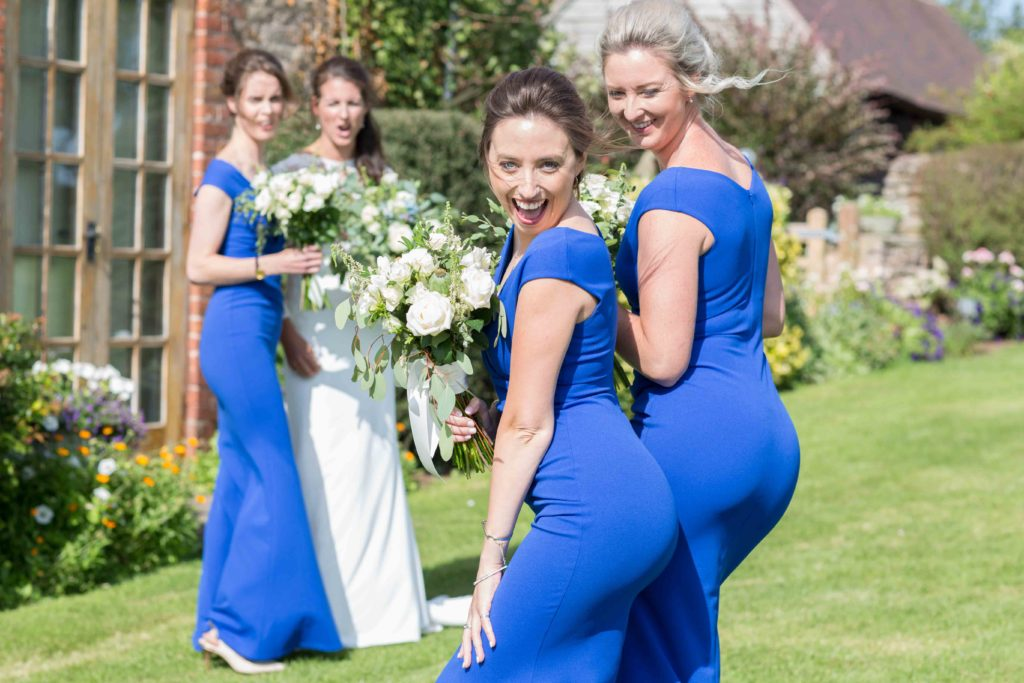 Cotswolds Wedding Photography, Herefordshire, Mintridge, two bridesmaids in blue dresses posing and laughing with bride and other bridesmaid in background looking on