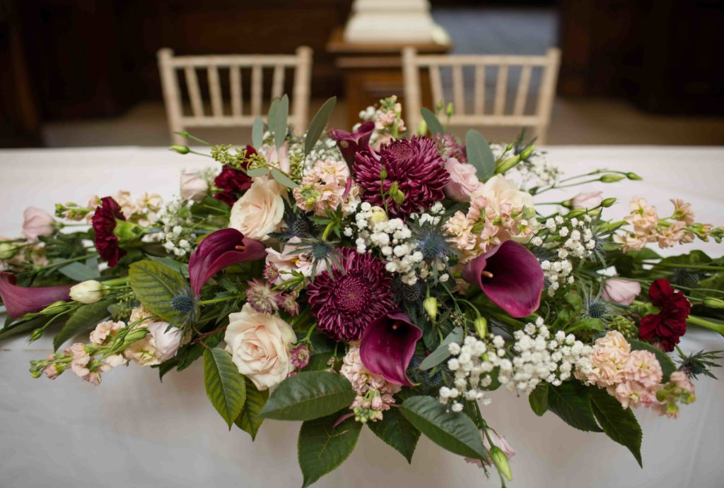Flower arrangement on table, wine red and white roses with green and white foliage