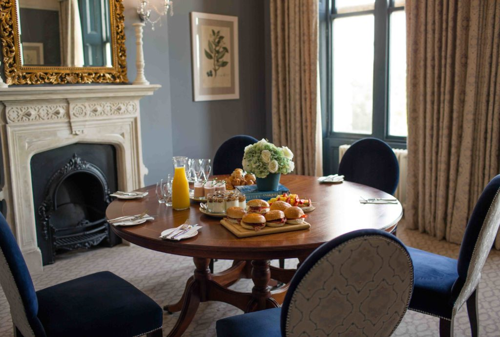 Clevedon Hall, Wedding, elegant round wooden table with lunch laid out - orange, burgers and light streaming through window