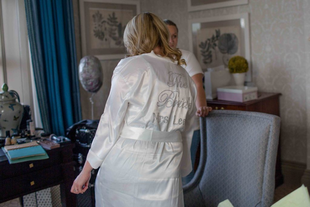 Clevedon Hall, Wedding, Bride dressed in silk dressing gown stood up with her back to the camera