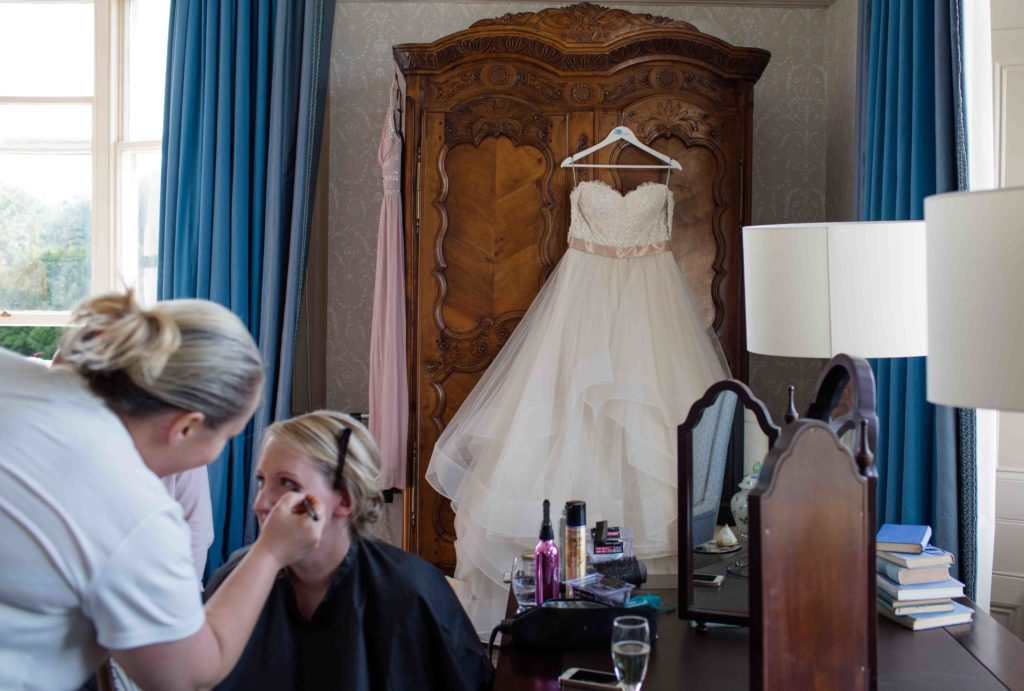 Clevedon Hall, Wedding, Bride sat down having her makeup applied with wedding gown hanging on wardrobe in back ground