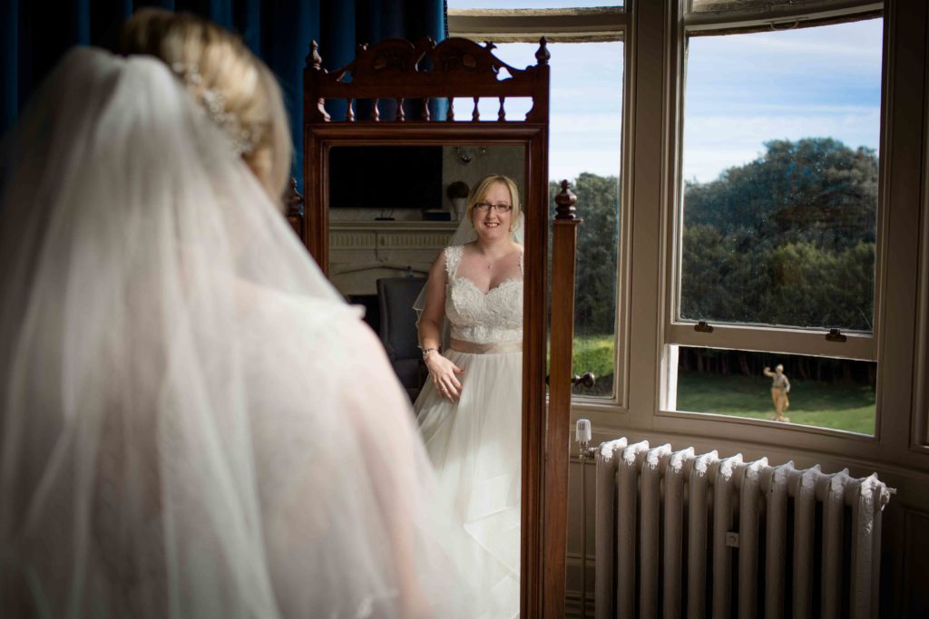 Clevedon Hall, Wedding, Bride dressed in her wedding gown looking in mirror with window the right of mirror