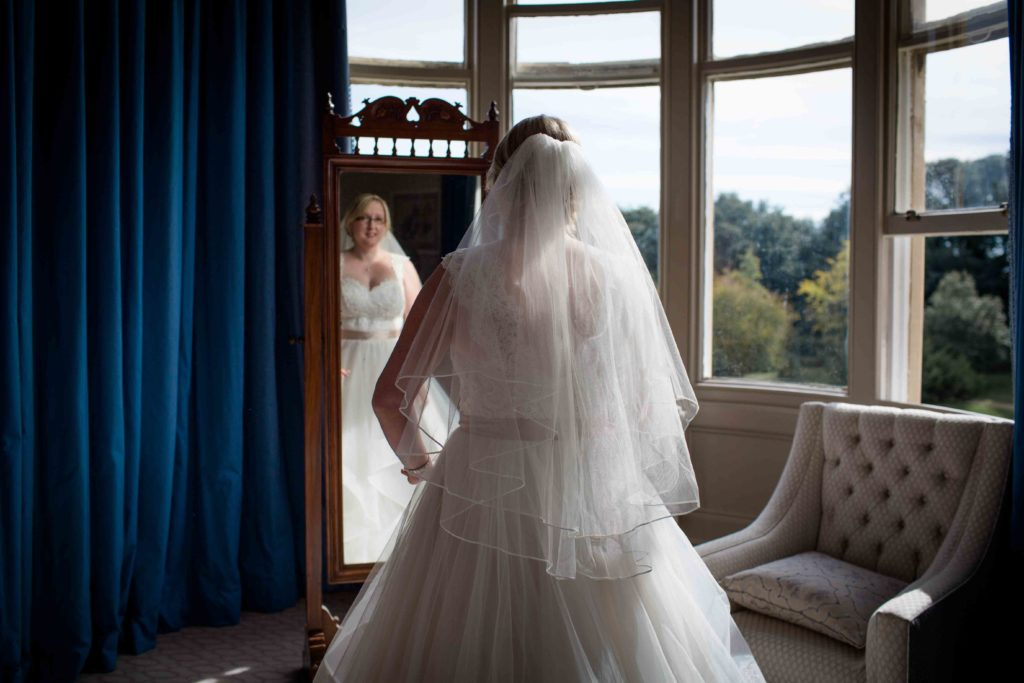 Clevedon Hall, Wedding, Bride in wedding gown looking at full length image in mirror