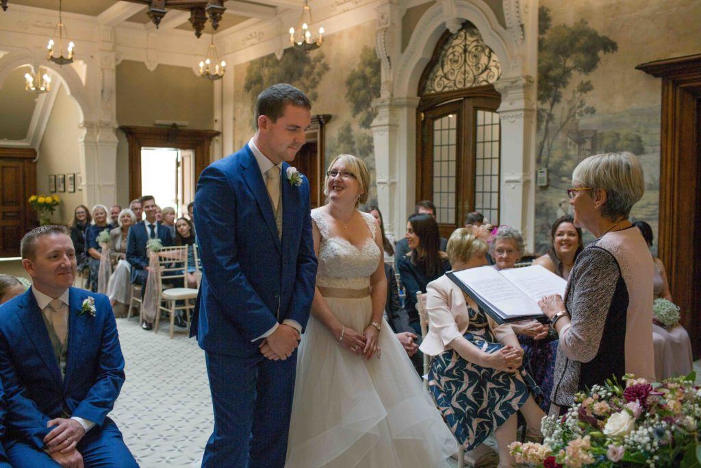 Clevedon Hall, Wedding, Bride and Groom, dressed in blue suit, stood together at top of aisle while ceremony words being read out