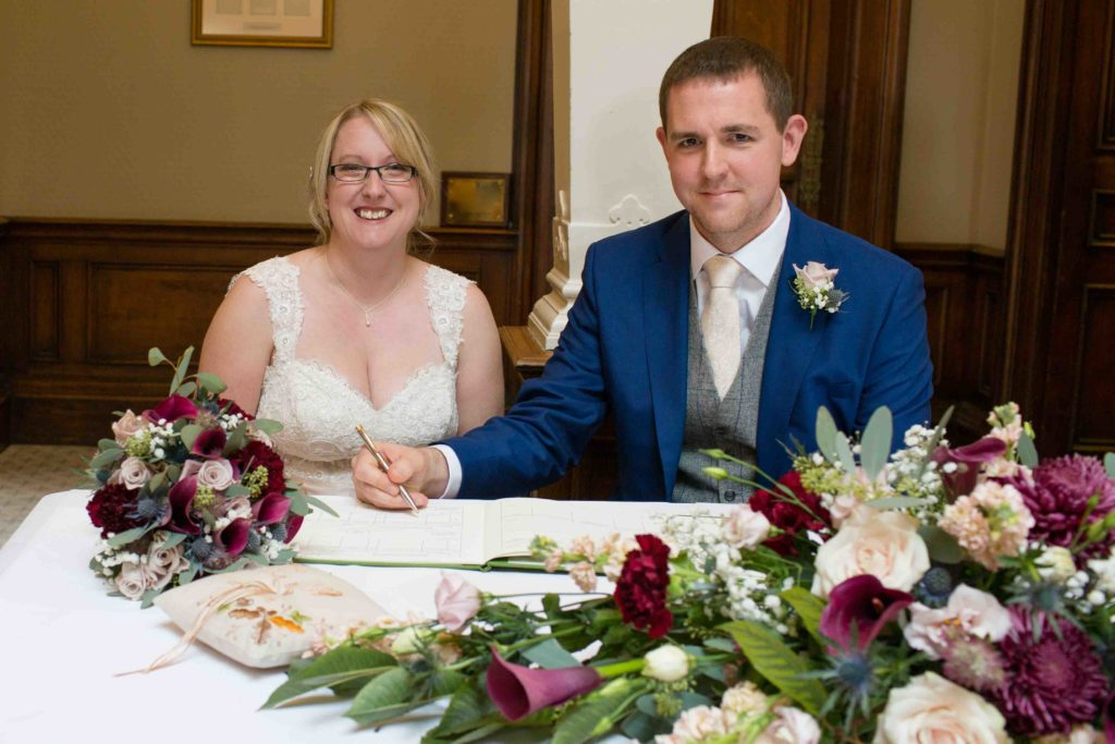 Bride and Groom sat signing wedding register, red roses on table in foreground