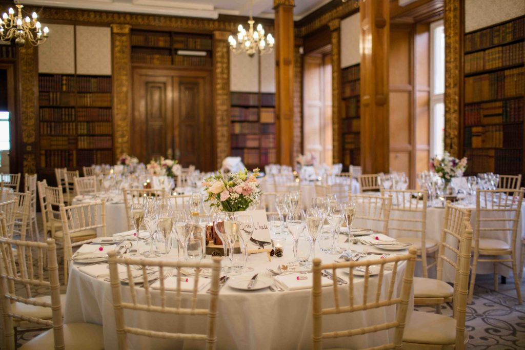 Clevedon Hall, dining area elegantly laid out for a wedding, white and cream decor with glasses and flowers as a center piece.