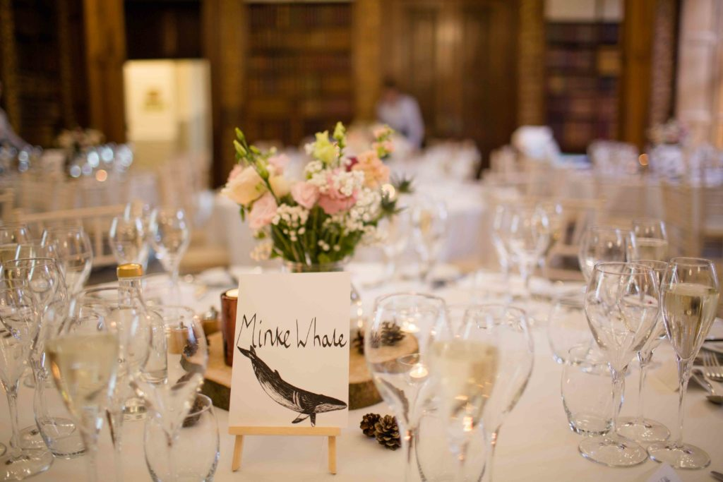 Clevedon Hall, dining area elegantly laid out for a wedding, close up of table with white and cream decor with glasses and flowers as a center piece.