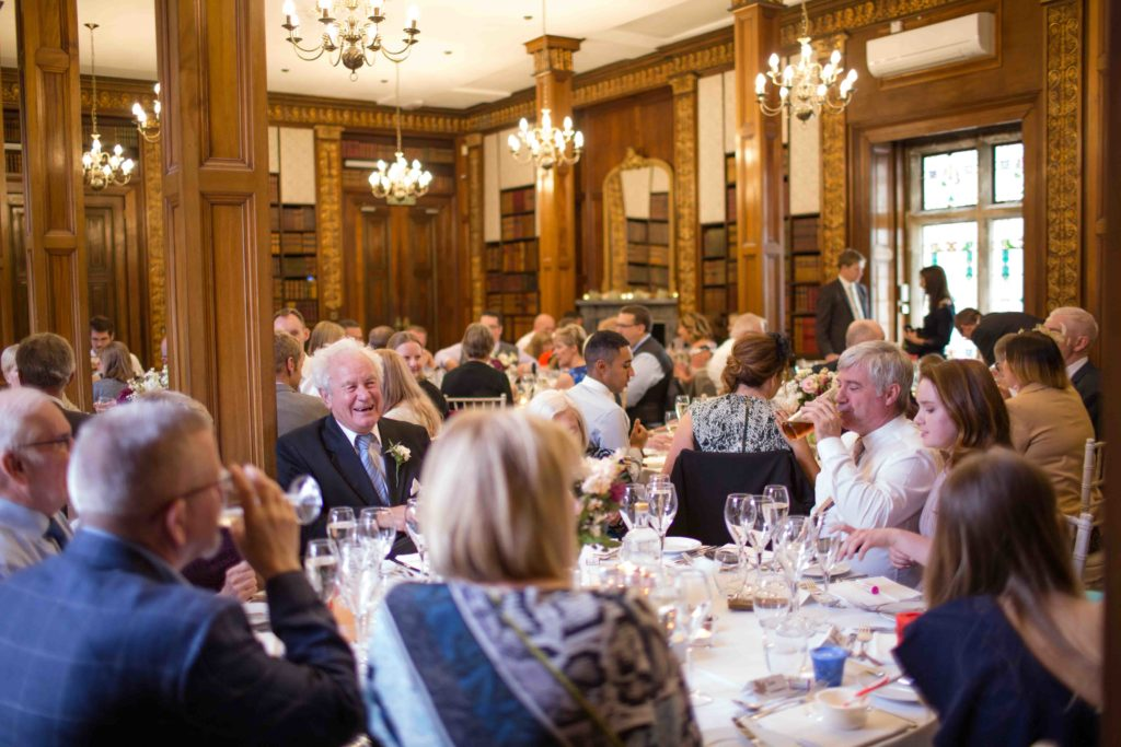 Clevedon Hall, wedding guests sat in dining area talking, listening and laughing