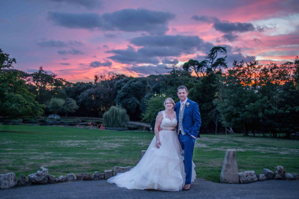 Cevedon Hall, Grounds, Wedding, Bride and Groom stood together with beautiful red sky, trees and lawns in background