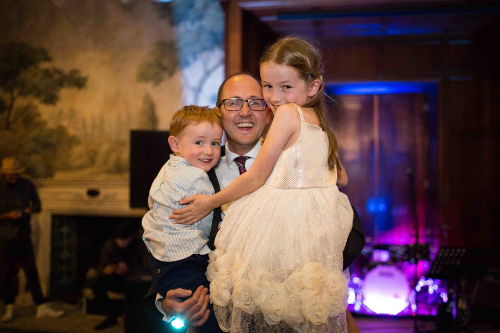 Wedding guests holding his young daughter and young son in his arms