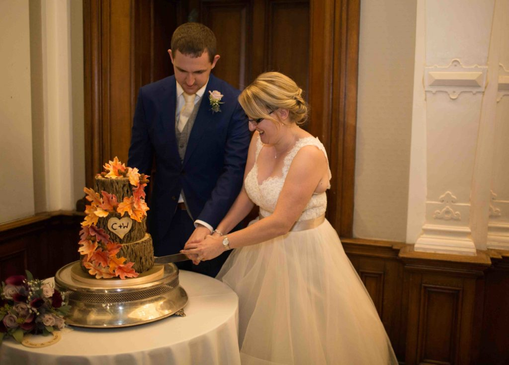 Clevedon Hall, Bride and Groom cutting naturally designed and decorated wedding cake