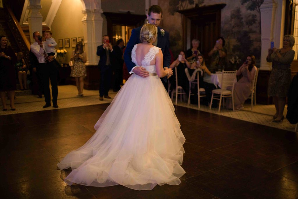 Cevedon Hall, Bride and Groom first dance in beautiful hall with dark wooden floor, view of back of brides dress