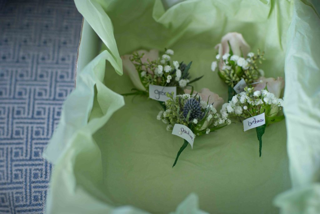 Light Green tray lined with light green tissue paper, contains white rose button holes with some green foliage,