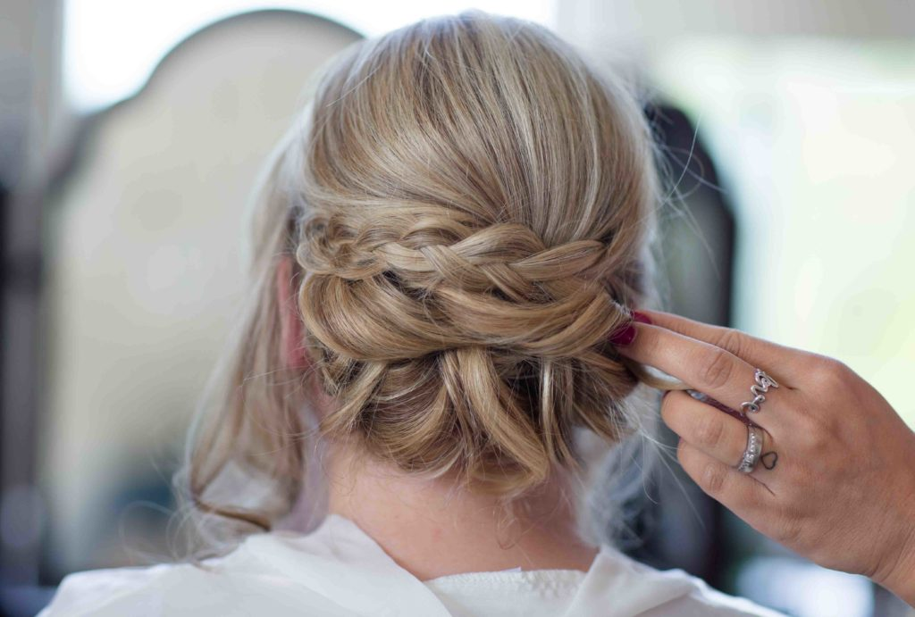 Clevedon Hall, Wedding, Bride dressed in silk dressing gown sat down and close up of the back of her hair in plaits