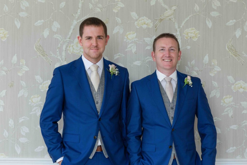 Clevedon Hall, Wedding, Groom and best man, both dressed in blue suits with grey waistcoats, smiling, stood against grey / white flower wallpapered wall.