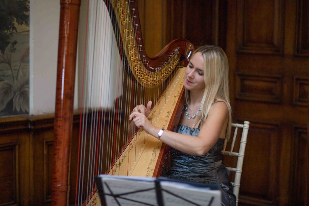 Wedding, woman with blond hair sat playing a  harp