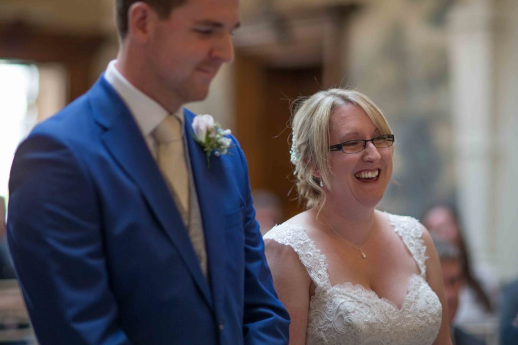 Bride laughing as words being read out while Groom stands next to her in blue suit.
