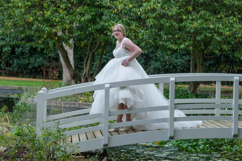 Clevedon Hall Grounds, Laughing bride crossing a grey wooden bridge