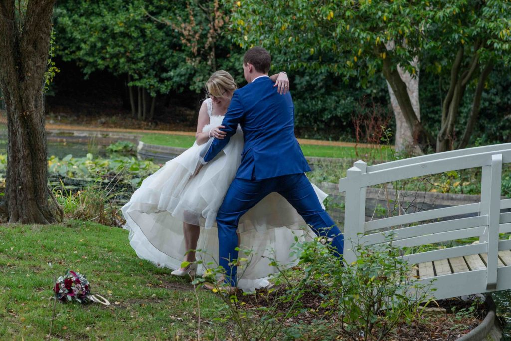 Clevedon Hall Grounds, Groom helping laughing bride step off a grey wooden bridge