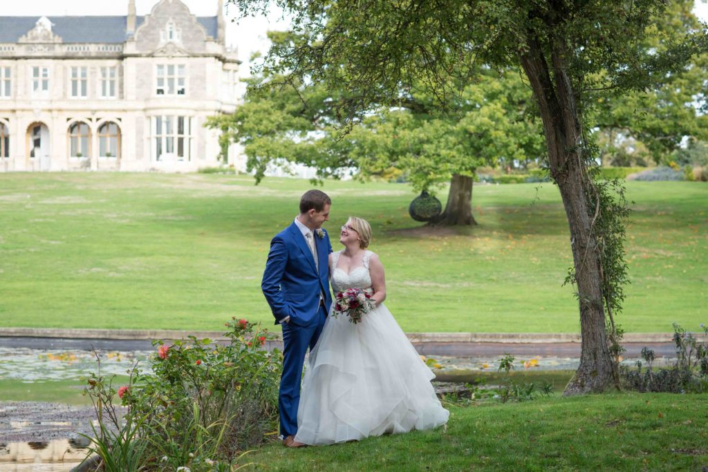 Clevedon hall, Wedding, Bride and Groom stood looking at each other, with lake and hall in back ground and tree overhanging
