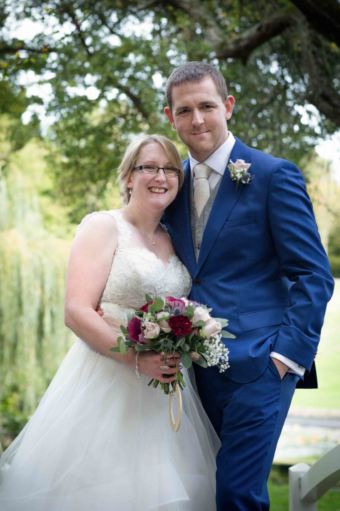Clevedon Hall Grounds, Bride and Groom smiling and stood holding each other