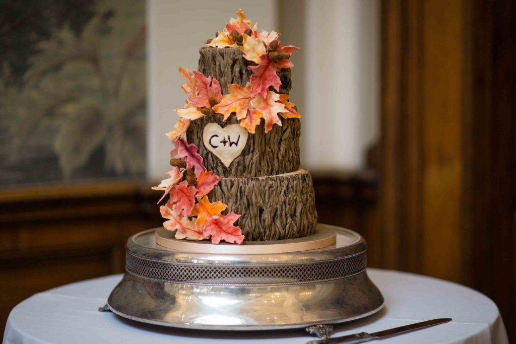 Wedding Cake, sat on round silver base, decorated naturally to look like a logs sat end on end in there tiers with autumn leaves and C&W in heart on second tier
