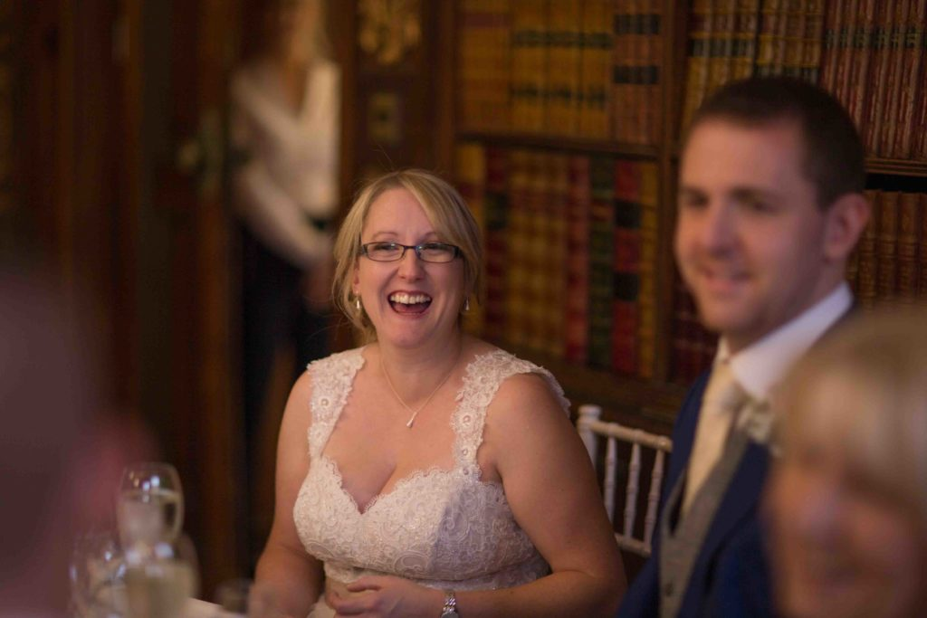 Clevedon Hall, Wedding, bride sat down leaning forward and laughing with groom smiling in foreground