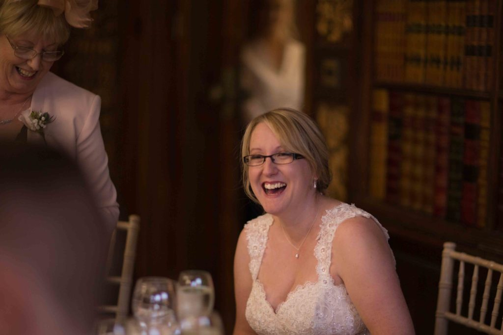 Clevedon Hall, bride sat down, leaning forward and laughing