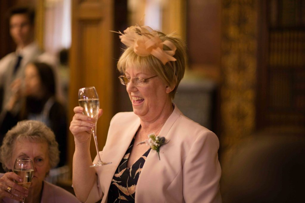 Clevedon Hall, dining area mother of bride in light pink jacket giving speech and toasting the happy couple