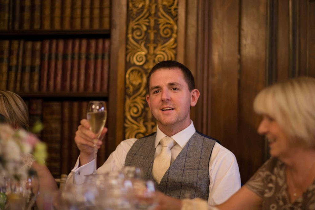 Groom, smiling while giving a speech and toasting the bride.