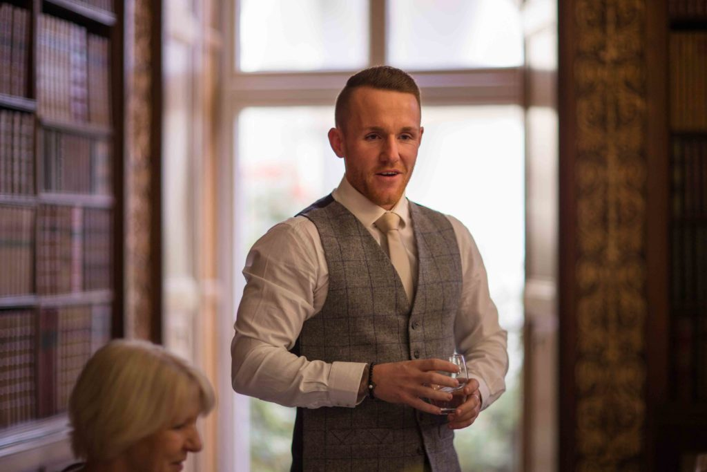 Clevedon Hall, Wedding, Best Man, grey waistcoat,  stood up and smiling while giving speech.