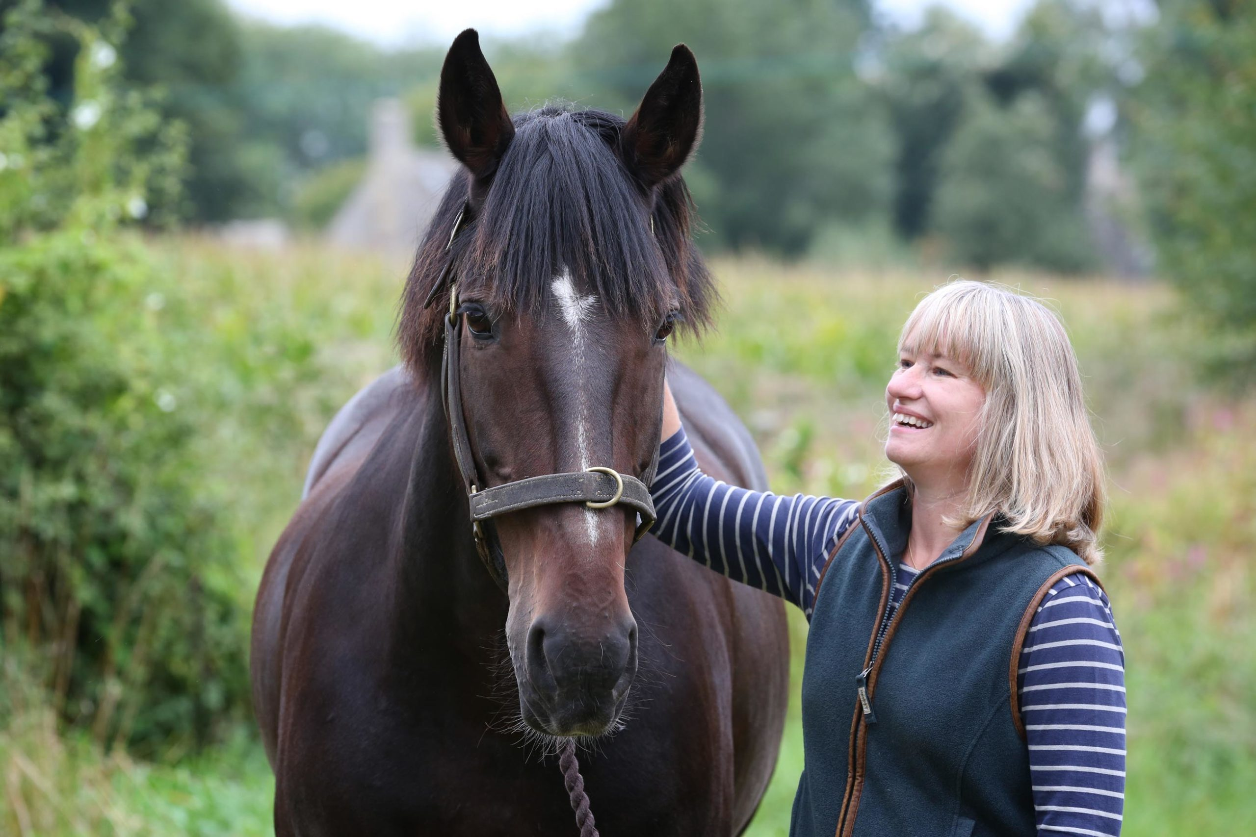 Cotswold Wedding Photographer, Helen Richmond, stood with hand on neck of dark bay horse named Bentley