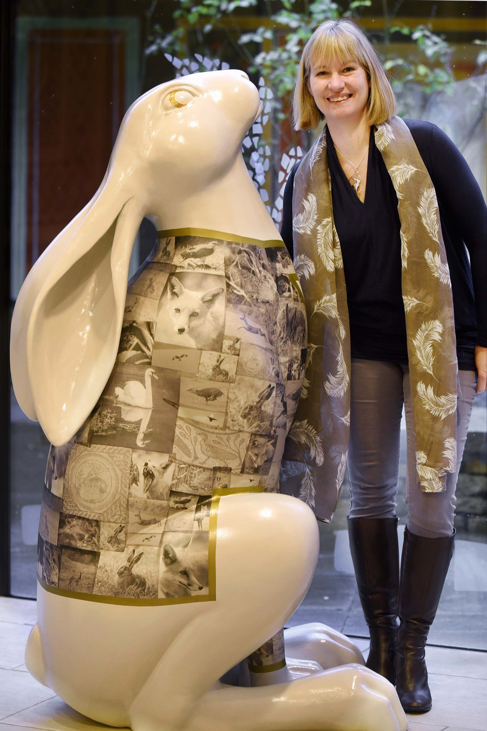 Cotswold Wedding Photographer, Helen Richmond, Corinium Museum, Stood next to large beige hare covered with Helen's photographs