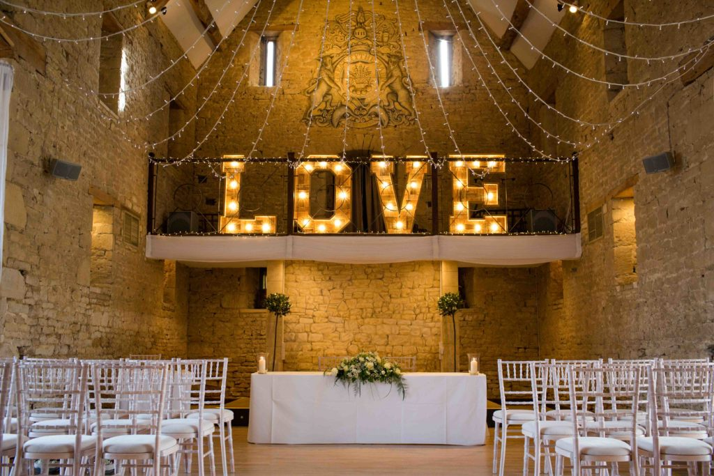 Great Tythe Barn Hall set up for wedding ceremony, with 'LOVE' in large neon letters on back wall.