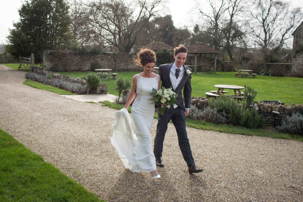 The Great Tythe Barn, Wedding, Bride walking down path, holding bouquet, arm in arm with Son