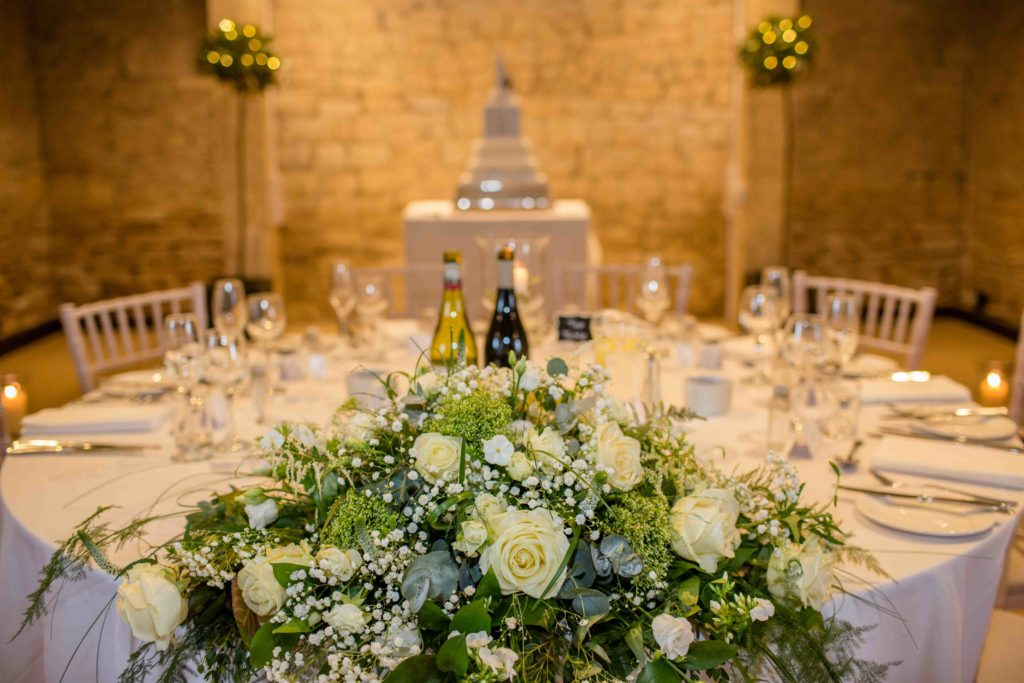 The Great Tythe Barn, Wedding Table Layout, White Roses and green foliage in foreground, cake in background and Cotswold stone wall